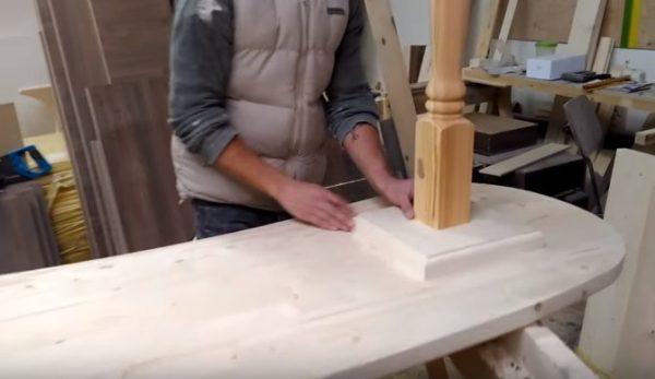 С помощью подкладки из доски ножку прикручивают к столешнице