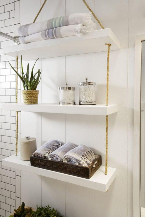 Белые полки на прочных веревках в скандинавской ванной