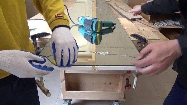 При отделении зеркала от поверхности шкафа разумно будет снять дверку с петель и уложить ее горизонтально, дабы стекло не слетало на пол как попало