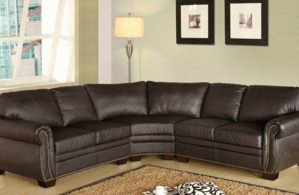 Угловой темный диван выразительно смотрится на светлом фоне