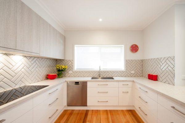 Если одну или две стены оставить без навесных шкафов, то интерьер с П-образным гарнитуром будет восприниматься легче