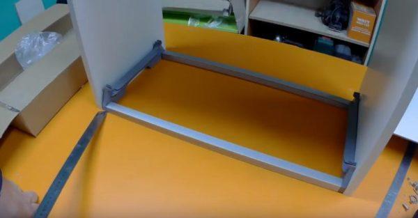 Примеряют рамку к стенкам шкафчика