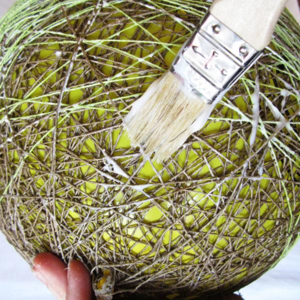 Когда достаточное количество ниток будет намотано на шарик, можно слегка пройтись кистью с клеем в тех местах, где его недостаточно