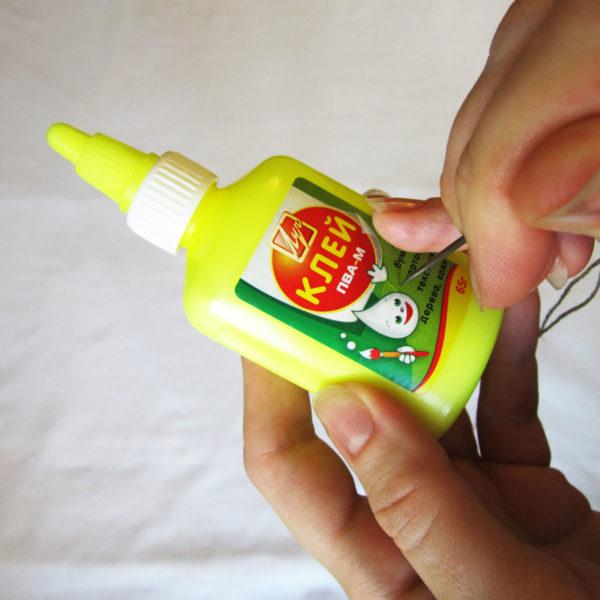 Вдеть нитку в иголку и проткнуть бутылочку с клеем ближе ко дну баночки, так будет намного удобнее, когда клей будет заканчиваться