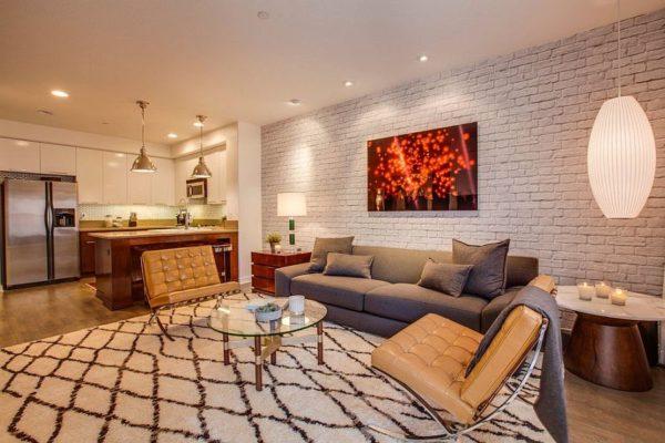 Белая кирпичная стена в гостиной, объединенной с кухней