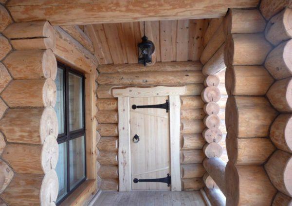 Деревянная дверь в доме из бревна