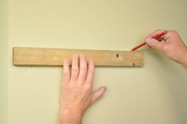 На стене делают пометки для креплений